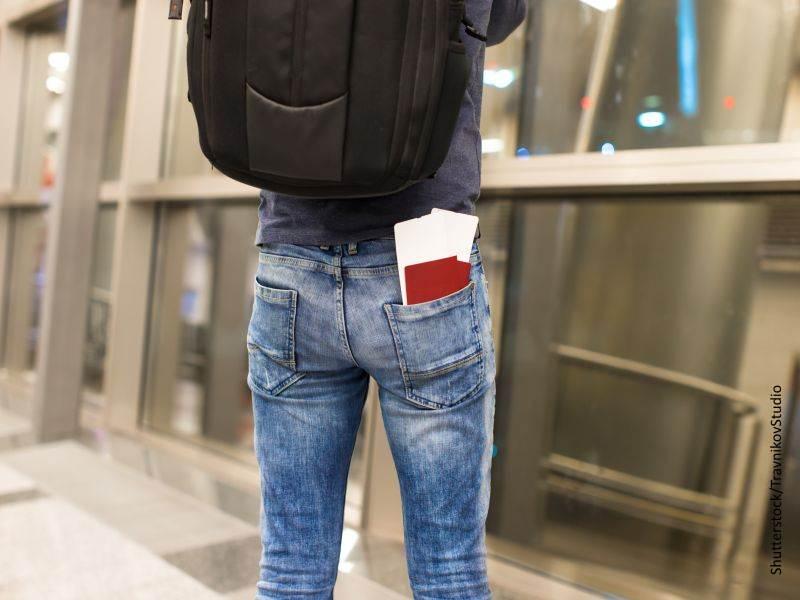 Espalda de un joven con mochila y unos billetes de avión con un pasaporte en su bolsillo del pantalón vaquero