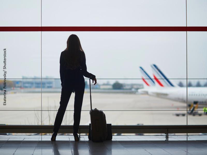 Chica con maleta mirando pista de aterrizaje del aeropuerto