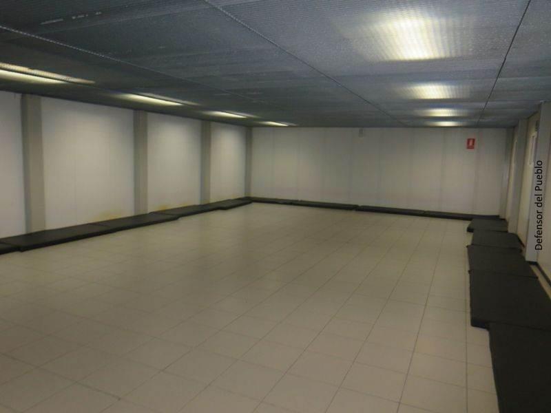 Sala con colchonetas negras alineadas a un lado en Primera Acogida en el Puerto de Almería