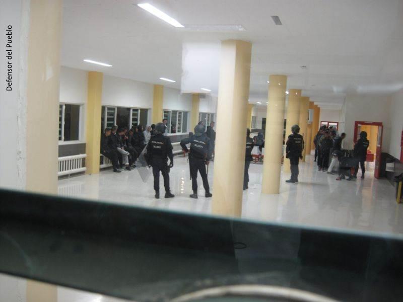 Acceso al comedor de la Cárcel de Archidona donde se encuentran varios efectivos de la policía con cascos y un grupo de jóvenes sentados