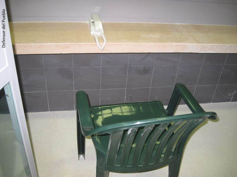 Locutorio de la Cárcel de Archidona, con teléfono y silla verde de plástico
