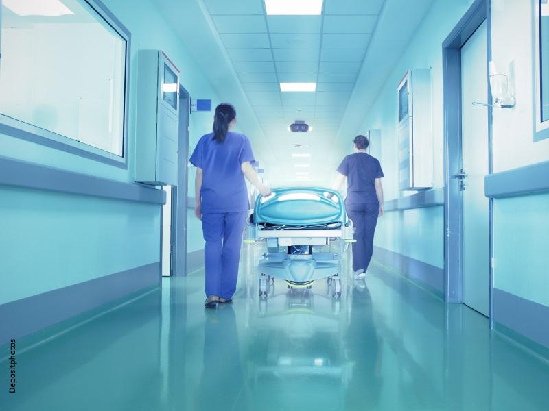 Dos enfermeras llevan una camilla por un pasillo de hospital muy luminoso