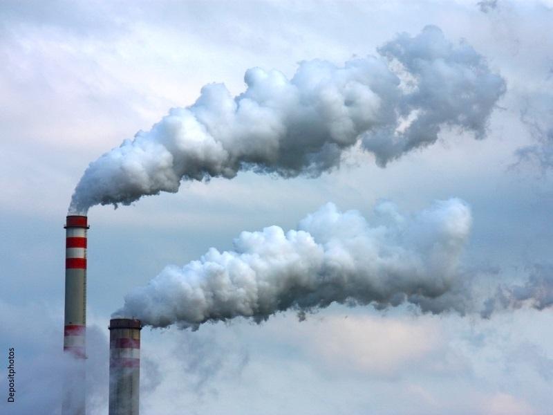 Dos chimeneas emitiendo humo contaminante