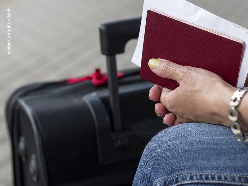 Mujer sentada con documentación en la mano y maleta al lado