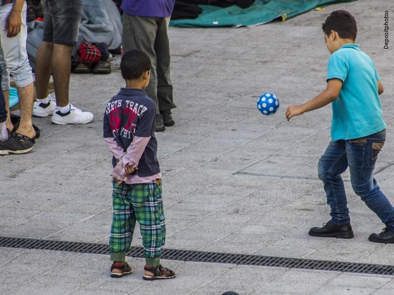 Niños inmigrantes jugando al balón en una calle
