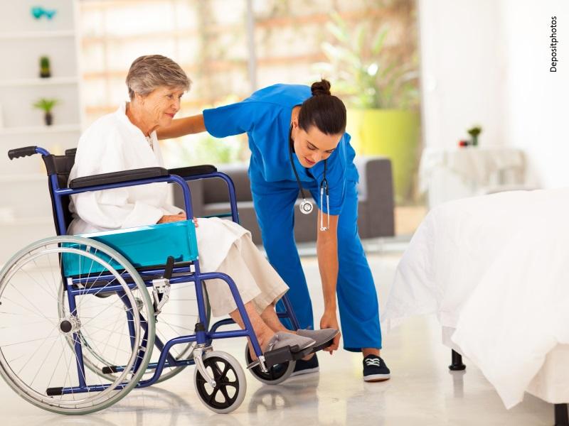 Enfermera atiende a mujer mayor en silla de ruedas