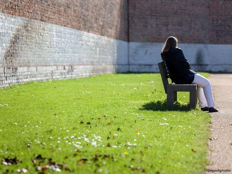 Mujer de espaldas sentada en un banco del patio de una cárcel