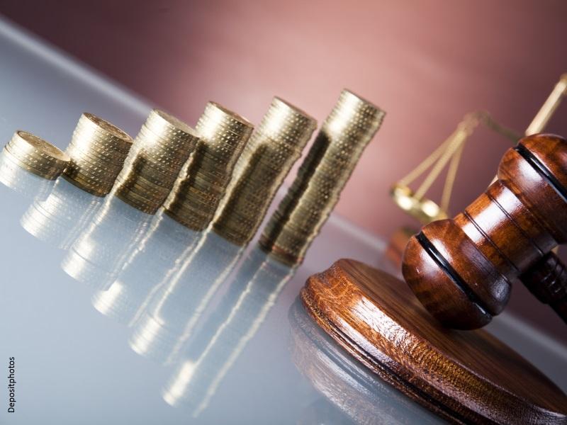 Vista de maza de Juez, balanza de la Justicia y monedas apiladas en varios montones