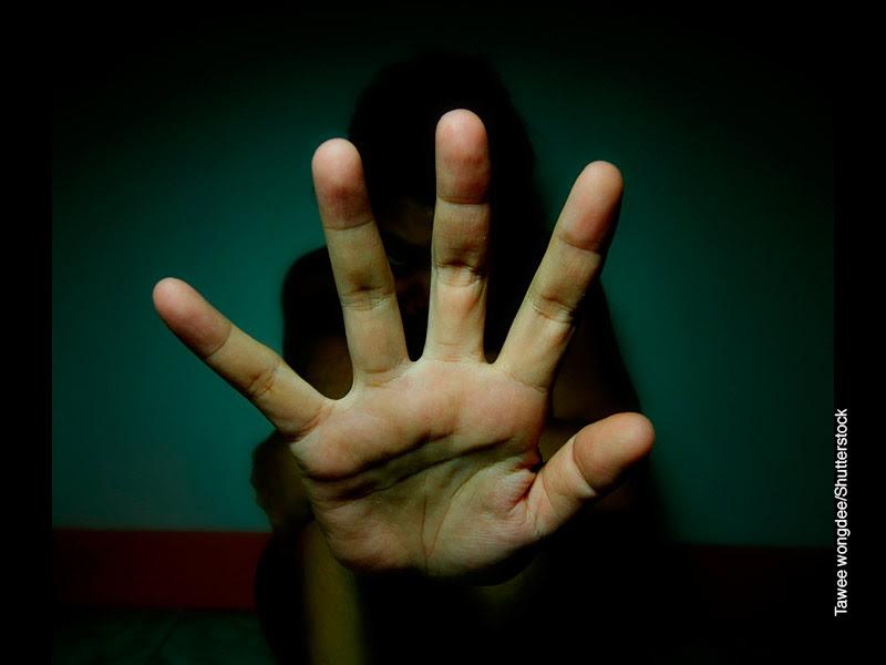 Primer plano de mano de mujer abierta sobre fondo oscuro y lo que parece una silueta de mujer