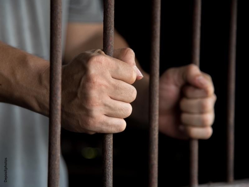 manos de preso agarrando los barrotes de la celda