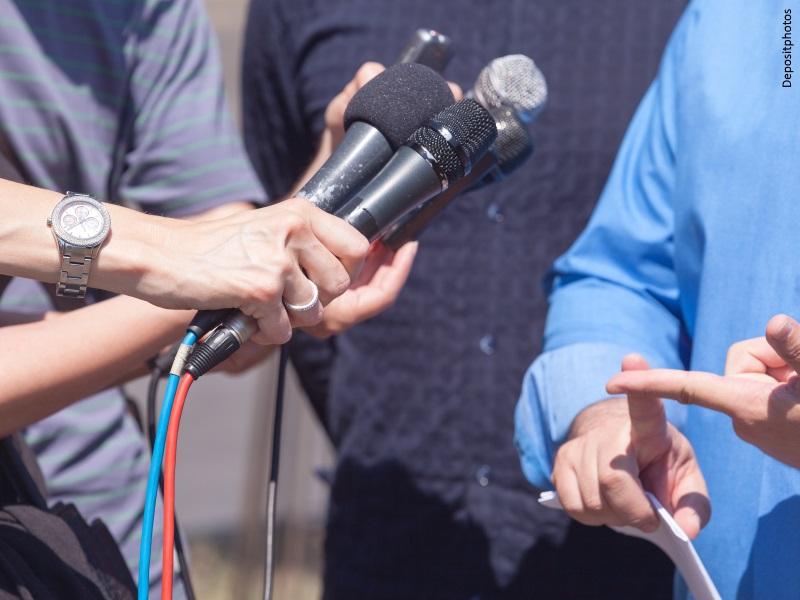 Periodistas con micrófonos entrevistado a hombre