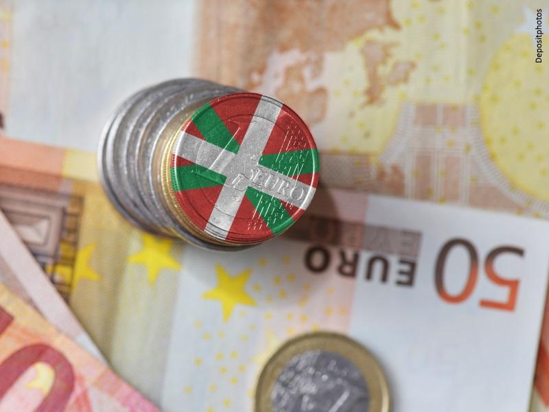 Billetes y monedas de euro, una de ellas forrada con la bandera de Euskadi