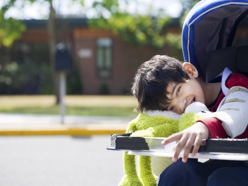 Menor con discapacidad sentado en silla recostado sobre un muñeco de peluche